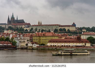 View of Hradcany Prague Castle and a boat on the Vltava river in the capital of the Czech Republic in a rainy day, horizontal image
