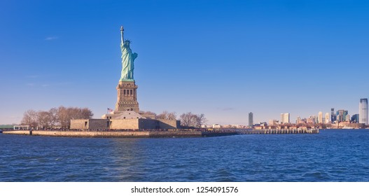View from the Hudson River, at dusk, of the Statue of Liberty and its island, where many tourists, go to visit it every day, from Manhattan.