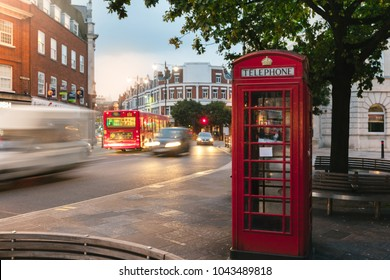 a view of the iconic red telephone box in London with moving cars in the background