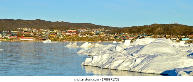 View of Ilulissat town with icebergs in front, the photo taken from the boat trip in Disko Bay, Greenland
