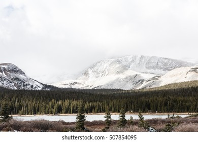 View of the Indian Peaks Wilderness in Winter with Pine Trees, a Lake, and Snow