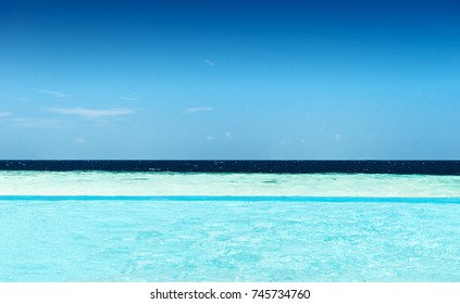 view from a infinity pool on the ocean with different shades of blue