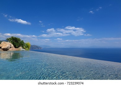 View from infinity pool overlooking the sea on sunny blue sky day