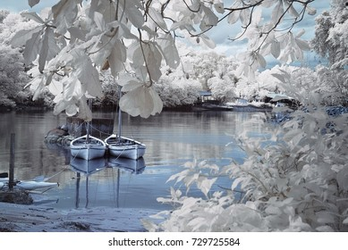 A view of infrared photography with two boats by the lakeside surrounded by trees with white color foliage.