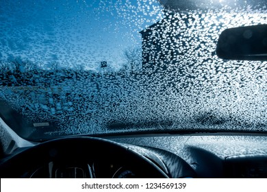 View from inside of automobile with windshield covered in frozen snowflakes. Winter driving conditions.