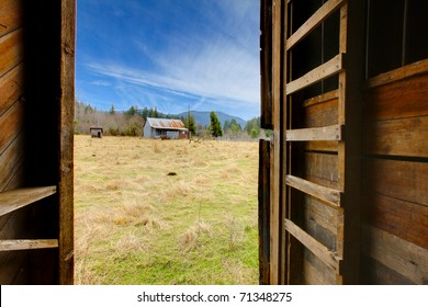 View from inside of the barn to the farm land with shed and field. Build in 1907 diary farm near Mt. Ranier in Washington State