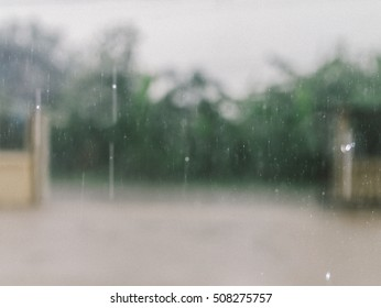 view from inside the building when raining. soft focus, blurred background. color in film style with little grain effect.