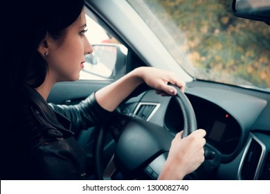 View from the inside of a car on attractive woman waiting patiently in car. Cute brunette girl sitting and holding the wheel looking ahead. Female driver waiting in vehicle with switched off engine