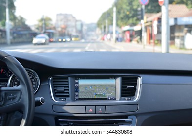 View from inside a car on a part of dashboard with a navigation unit and blurred street in front of a car