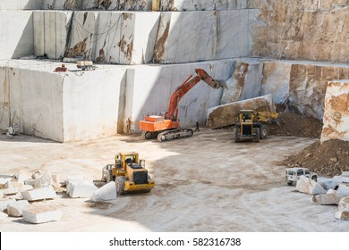 View inside Carrara marble quarry with heavy machines moving a marble block