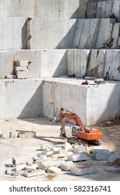 View inside Carrara marble quarry with marble blocks and an orange excavator taking a break