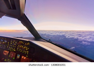 View from inside cockpit at copilot seat when airplane flying at high altitude over the clouds in the sky. Seen in the evening sunset with beautiful twilight at horizontal skyline. Modern aviation.