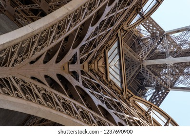 View to the inside of Eiffel Tower. Big symetrical building. Close up shot in the morning. Blue sky with a sunny weather. Paris, France