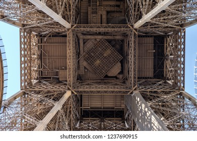 View to the inside of Eiffel Tower. Big symetrical building. Close up shot in the morning. Blue sky with a sunny wheather. Paris, France
