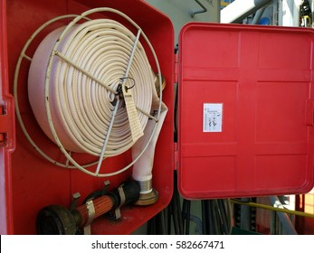 View of inside the fire hose cabinet where fire hose, nozzle, f key and wrench are stored, ready to be utilized in case of fire emergency.