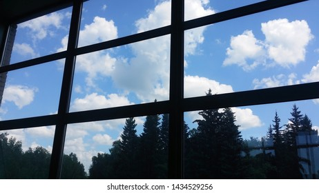 View from inside  of an office building through a large window  at the sky with cumulus clouds on background and at a coniferous forest.