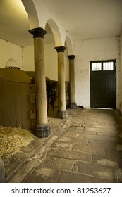 View inside old stable block with stone floors and copy space.