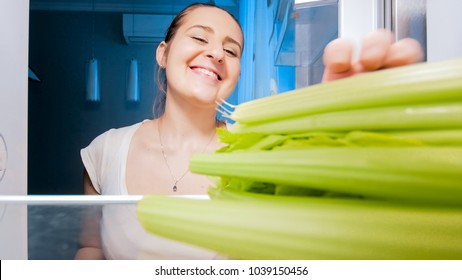 View from inside of refrigerator of smiling woman taking celery