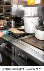 A view inside a restaurant kitchen. The hands of a cook prepares several pans of ingredients for the next food order.