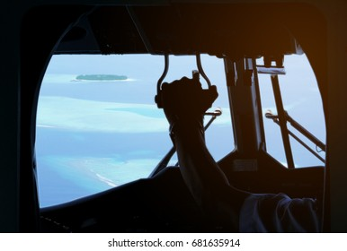 View from inside seaplane cockpit looking out to bright famous beach destination Maldives small islands atoll. Inside plane is dark, so we see pilot's arm, hands, and aircraft parts in silhouette.