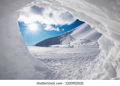 view from inside of a  snow grotto into bright winter landscape in the austrian alps