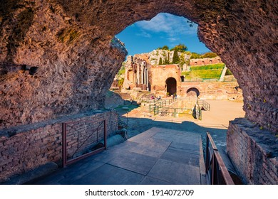 View from inside the stone arch of ruine of Greco-Roman theater, Sicily, Itale, Europe. Bright morning cityscape of Taormina town and Etna volcano on background. Traveling concept background. - Shutterstock ID 1914072709
