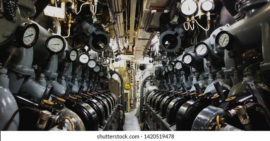 View of the inside of a submarine with the engine and pressure gauge.