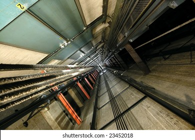 The view up inside a tall elevator shaft.