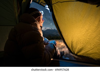 View from inside a tent on the male tourist have a rest in his camping at night. Man with a headlamp sitting in the tent near campfire under beautiful night sky full of stars and milky way
