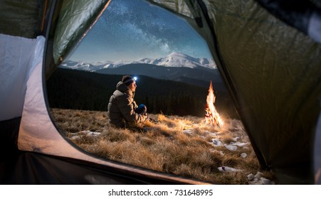 View from inside a tent on the male tourist have a rest in his camping in the mountains at night. Man with a headlamp sitting near campfire under beautiful night sky full of stars and milky way