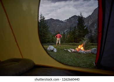 View from inside tent at sunset. Alone tourist, hiker standing at bonfire