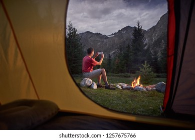 View from inside tent at sunset. Man hiker sitting at bonfire with cellphone