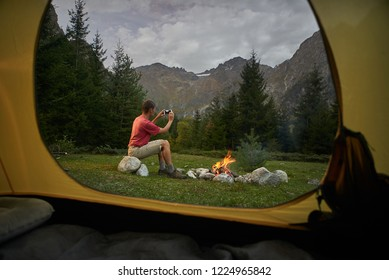 View from inside tourist tent. Man hiker sitting at bonfire, making selfie photo by mobile phone