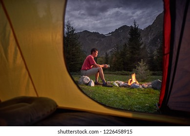 View from inside tourist tent at sunset. Alone tourist, man hiker sitting at bonfire