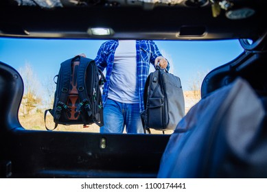 view from inside of trunk. young adult man putting bag in car trunk. car travel concept