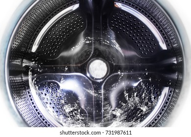 View inside the washing machine while washing laundry. Splashing water.