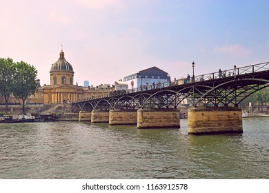 view of the Institut de France and pont des Arts, pedestrian bridge which crosses the River Seine from right bank of the Seine River in Paris, France