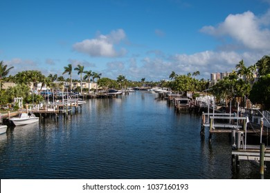 View of the intercoastal waterway smooth water boats docked buildings puffy white clouds blue sky