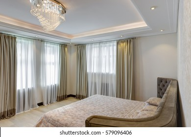 View of interior of big gray bed with headboard. Modern and stylish interior of bedroom with crystal chandelier in center of ceiling. White wall and so lighting room.