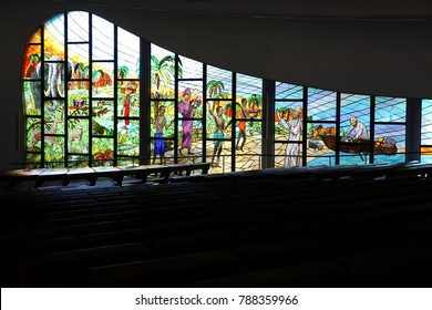 View of the interior of st Paul Cathedral in Abidjan city. Large colored stained glass windows and long wooden benches can be seen indoors. The picture has been taken on 13rd february 2016.