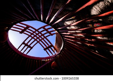 View from interior of traditional Kyrgyz yurt (tent) with roof poles and felt cover, crown of a yurt called tunduk is symbol in center of Kyrgyzstan nation flag.