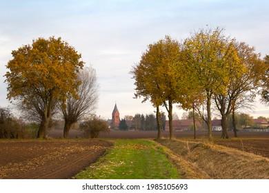 Mit Blick in die Herbstlandschaft kann man auch eine kleine Straße mit einer kleinen Kirche im Hintergrund sehen.