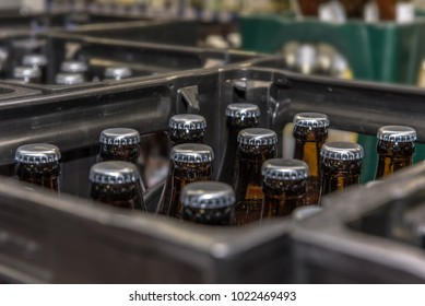 View into a beer crate standing in a beverage market. Crate with full beer bottles. Focus on the bottles. Concept: drinks