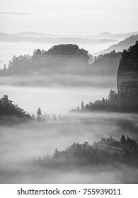 View into deep misty valley in Saxony Switzerland, Germany. Sandstone peaks and rocky hills sticking up from thick fog. Black and white picture.