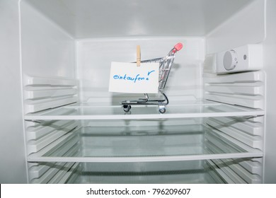 View into an empty refrigerator with a cart inside with a German notice to go shopping