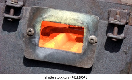 A view into the forge of a farrier. The horseshoe glows red in the intense heat.