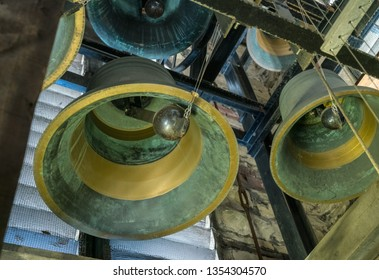 View into interior of large brass church bell in stone tower with pulley and bell clapper
