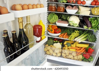 VIEW INTO OPEN FRIDGE WITH SHELVES STOCKED WITH FRESH FRUIT,VEGETABLES,GROCERIES,AND DRINKS