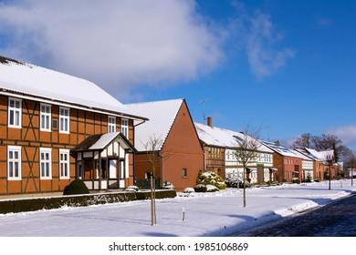 Blick in eine kleine Straße eines typischen Dorfes in der Altmark Region im Winter. Die Häuser sind entweder als halb bebaute Gebäude oder als Ziegelsteine gebaut.