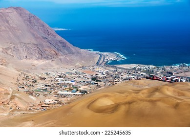 View of Iquique, Chile with sand dunes and Pacific Ocean visible